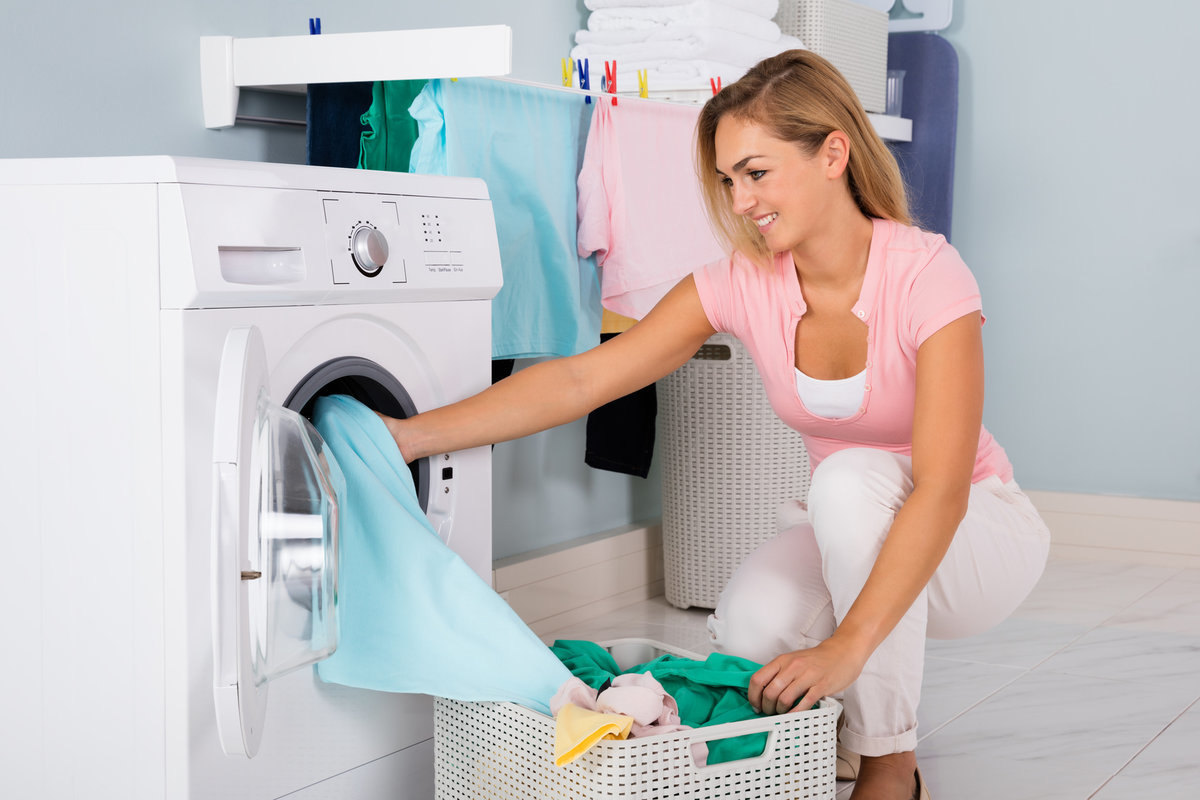 Young Smiling Woman Loading Dirty Clothes In Washing Machine In Utility Room