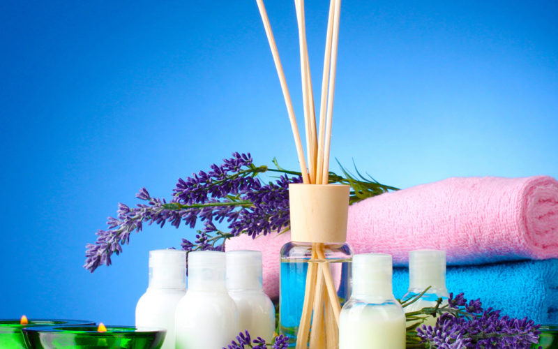 Bottle of air freshener, lavander, towels and candles on blue ba